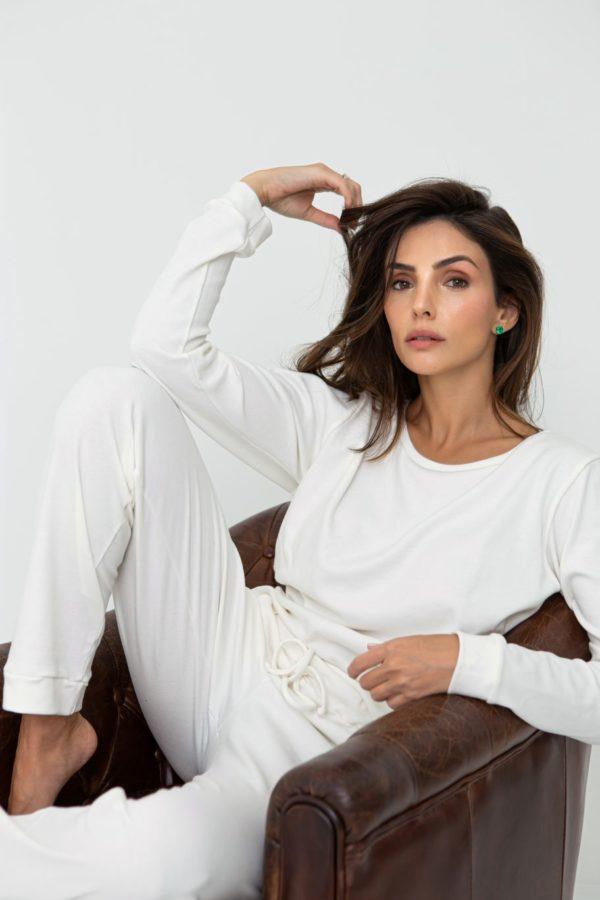 Pessoa veste pijama na cor branco calça e camisa manga longa