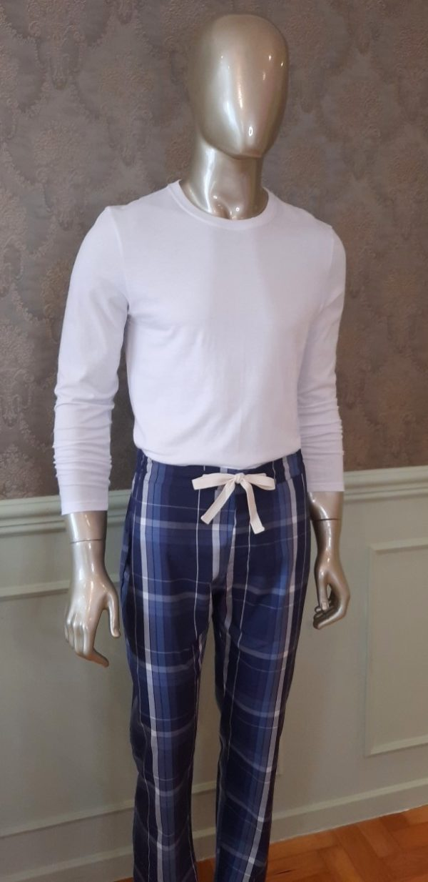 Manequim veste camisa manga longa na cor branca e calca com estampa xadrez