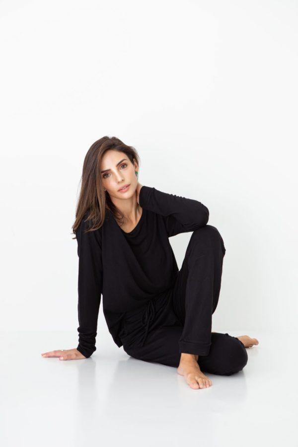 Pessoa veste pijama na cor preta calça e camisa manga longa