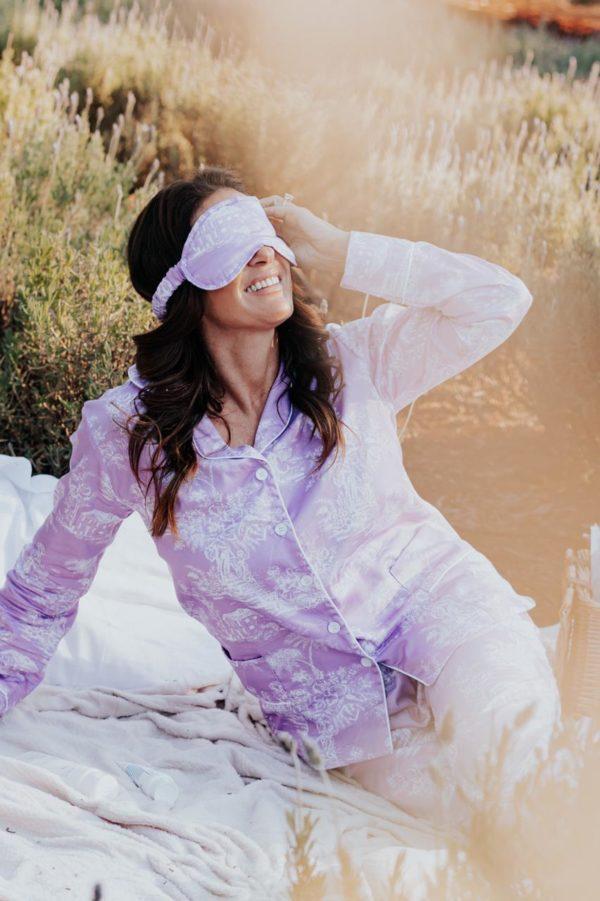 Mulher veste pijama e máscara de dormir Toile de Jouy Lavanda, num campo de lavanda que remete aos sonhos