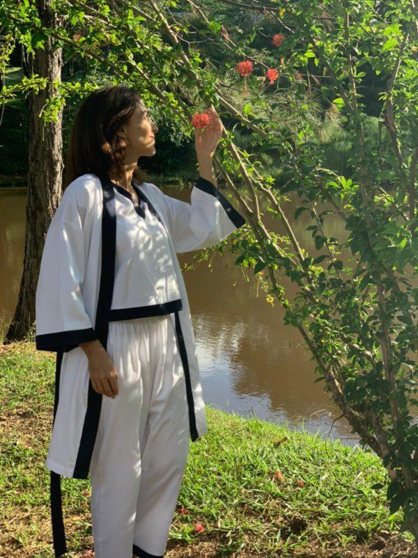 Pessoa veste robe curto na cor branca com um conjunto de camisa e capri branca