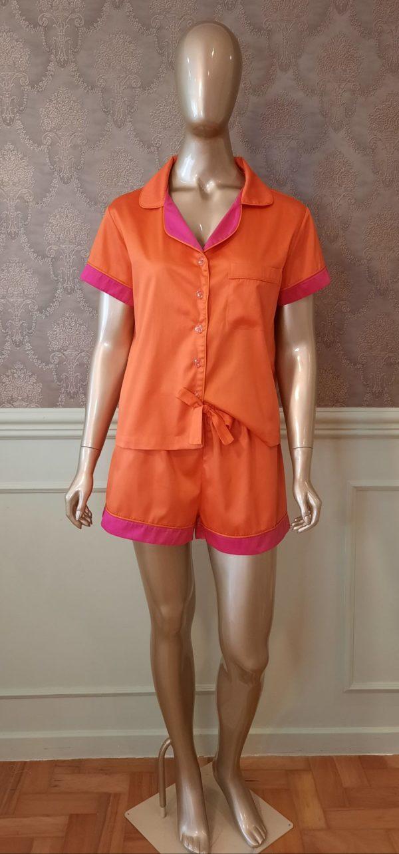 Manequim veste pijama short e camisa manga curta na cor laranja com detalhes pink