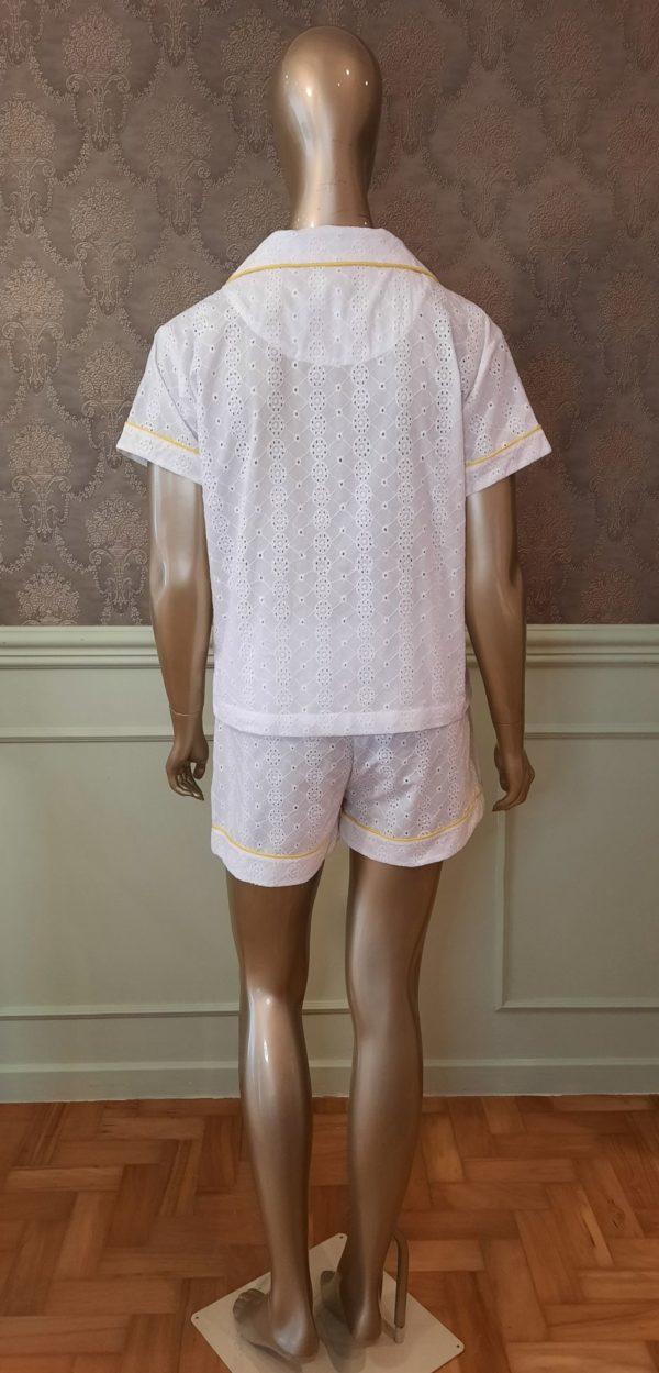 Manequim veste pijama short e manga curta na cor branca com debrum amarelo